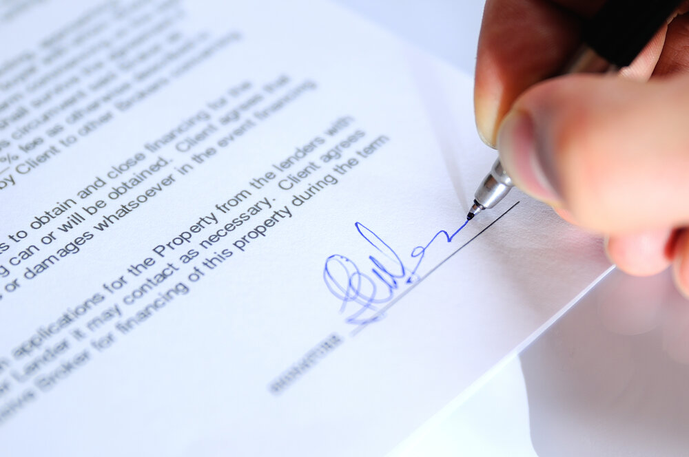 Businessman signing a document closeup